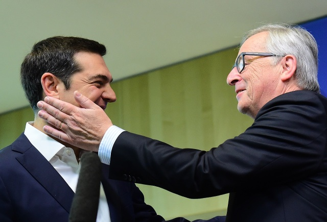 Greece's Prime Minister Alexis Tsipras (L) is welcomed with a friendly tap by European Commission President Jean-Claude Juncker ahead of an emergency leader's summit on Greece at the European Commission in Brussels,on June 22, 2015. AFP PHOTO/Emmanuel Dunand