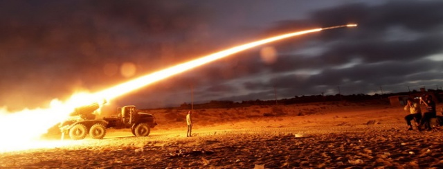Rebel fighters fire a Grad rocket at the front line west of Misrata, Libya, Monday, June 20, 2011. (Hassan Ammar/Associated Press)